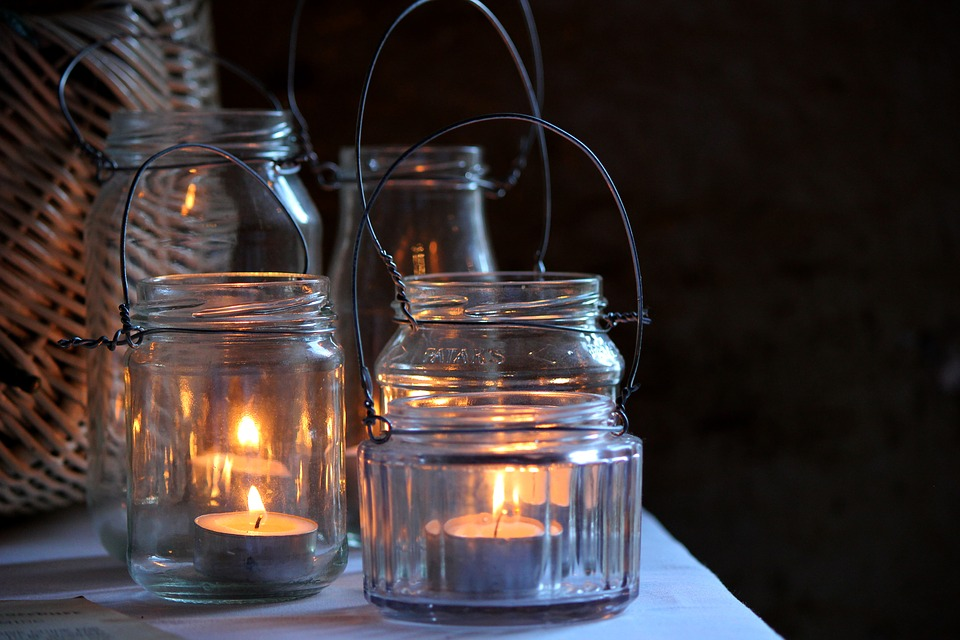 Photo with mason jars repurposed as candle holders with handles.