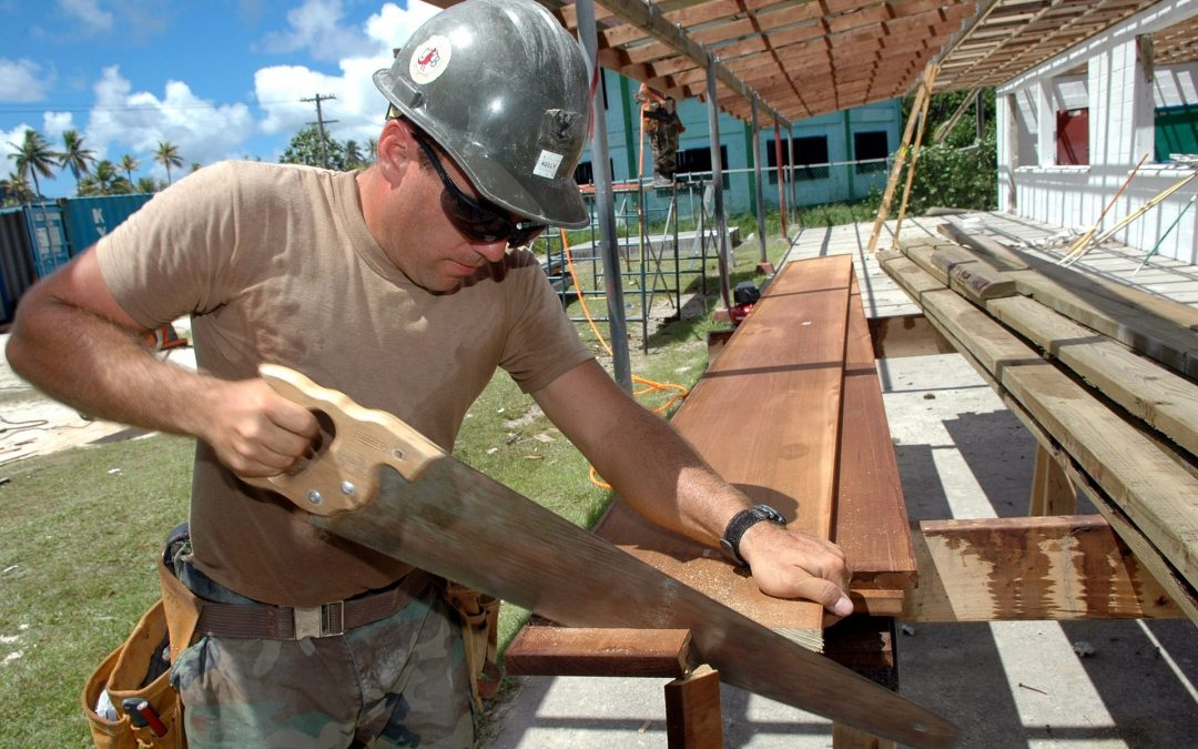 Construction worker is cutting a wood using saw